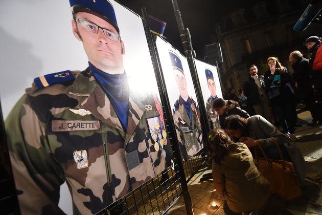 Des personnes allument des bougies le 26 novembre 2019, devant la mairie de Pau, au pied des portraits...