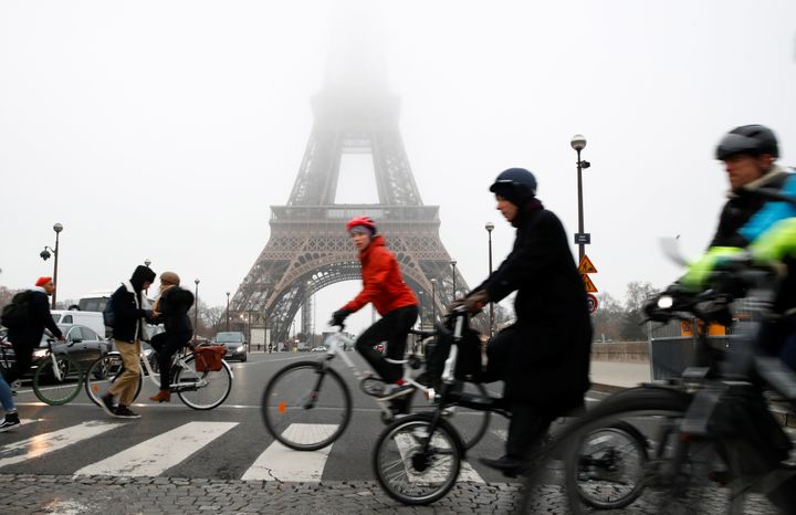 People ride bicycles near the Eiffel Tower during a strike by all unions of the Paris transport network (RATP) as part of a d