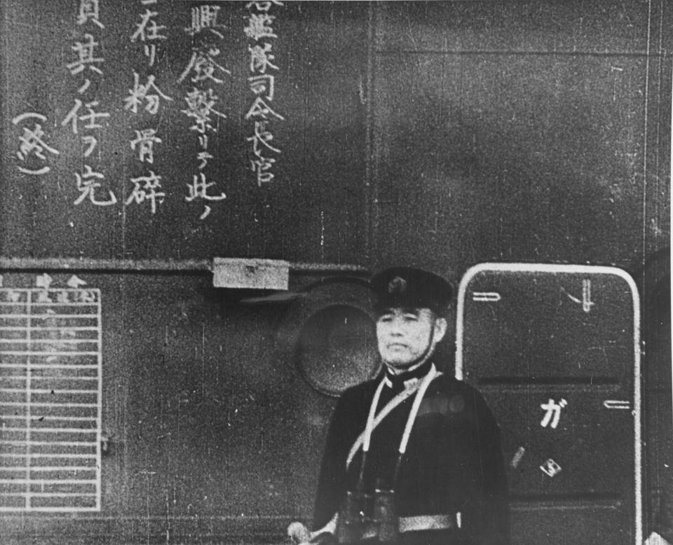 12月7日、真珠湾攻撃に向かう戦闘機を見送る空母「翔鶴」の乗組員。には、空母の外壁には、パイロットへの攻撃指令が漢字でつづられている。