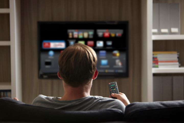 A man watches television on a smart TV in this undated stock photo. The FBI says it's important to know your TV's capabilities before buying one.