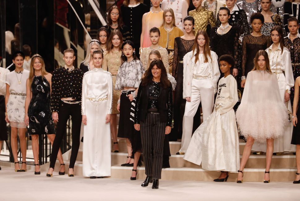 """French fashion designer Virginie Viard (C) acknowledges the audience as models pose with her creations at the end of the Chanel """"Metiers d'art 2019-2020"""" show at Le Grand Palais on December 4, 2019, in Paris, France. (Photo by FRANCOIS GUILLOT / AFP) (Photo by FRANCOIS GUILLOT/AFP via Getty Images)"""