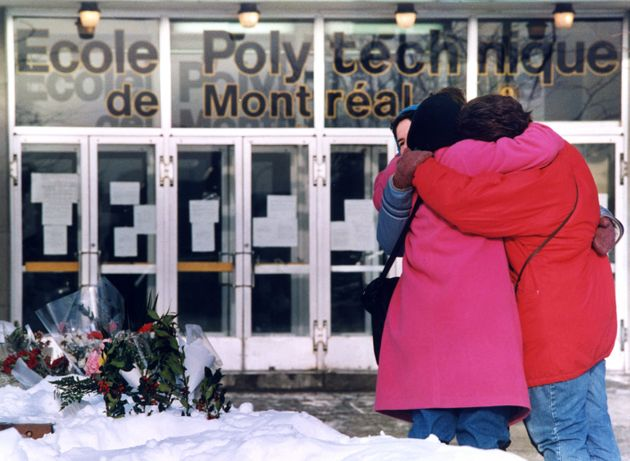 Three women hug each other after laying flowers in front of the Polytechnical School at the University of Montreal on Dec. 9, 1989.