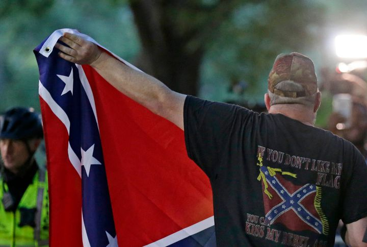 A man displays a Confederate flag during a rally regarding the recently vandalized Confederate monument known as Silent Sam a