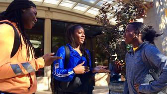 Kennesaw State University cheerleaders, from left to right, Kennedy Town, Shlondra Young and Tommia Dean talk outside the student center on the school's campus in Kennesaw, Ga., Monday, Oct. 16, 2017. The three are part of a group of cheerleaders from the Georgia college that say they will take a knee in the stadium tunnel when the national anthem is played at Saturday's homecoming game since their university moved them off the field after an earlier demonstration. (AP Photo/Jeff Martin)
