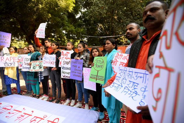 People hold placards during a sit-in protest against the Hyderabad rape-murder case and growing incidents...