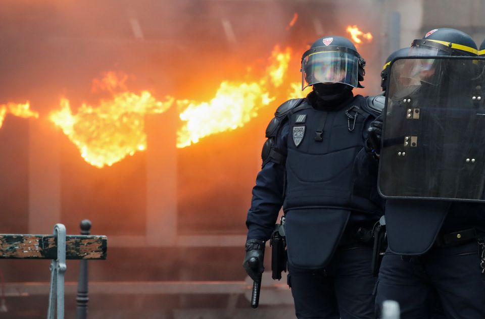 Policemen secure an area during a demonstration against French government's pensions reform plans, as...