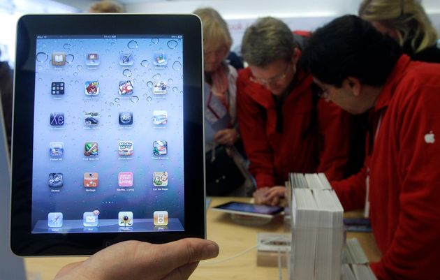 In this Nov. 26, 2010 file photo, a store employee holds up an iPad at an Apple Store in San