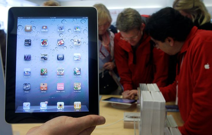 In this Nov. 26, 2010 file photo, a store employee holds up an iPad at an Apple Store in San Francisco.