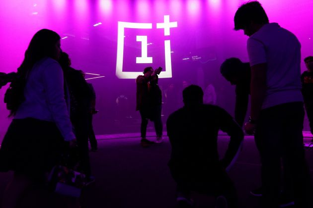 The OnePlus logo is projected onto a wall during a launch