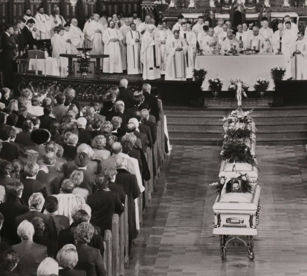 Four caskets lead to the altar where priests perform a high requiem mass for nine of the fourteen women...