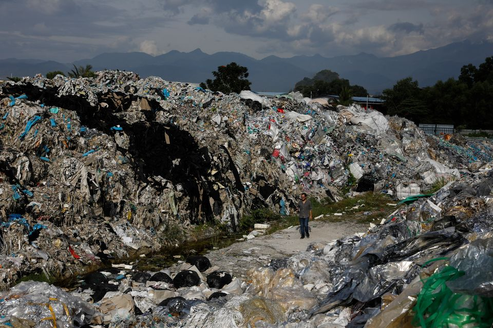 A man walks through an illegal dumpsite teeming with plastic trash imported from the United States, in...