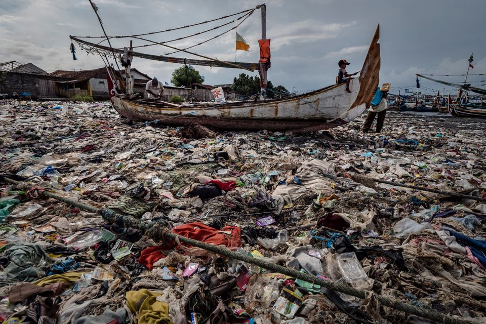 A boy paints a boat in a beach filled with plastic waste at Muncar port in Banyuwangi, East Java on March...