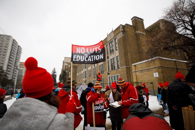 Striking teachers with the Ontario Secondary School Teachers' Federation walk the picket line outside...