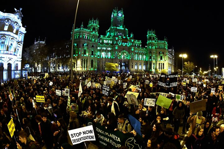 Demonstrators walk past the city hall on Cibeles Square during a mass climate march to demand urgent action on the climate cr
