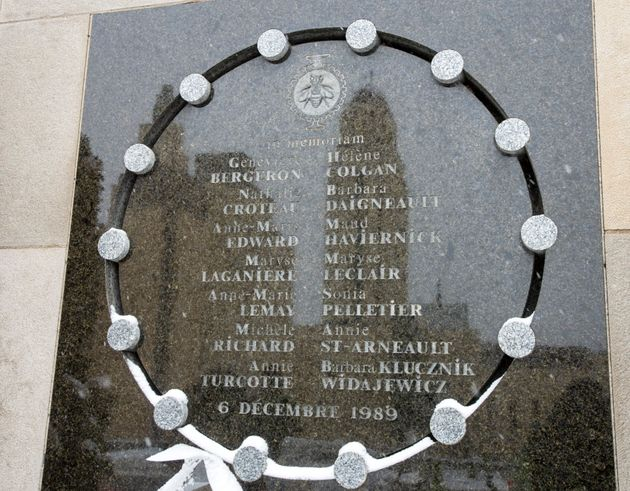 The tower of the University de Montreal is reflected in the school's memorial plaque that names the 14...