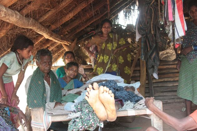 The family of a villager killed by Indian security forces sit by his corpse. Seventeen villagers were...