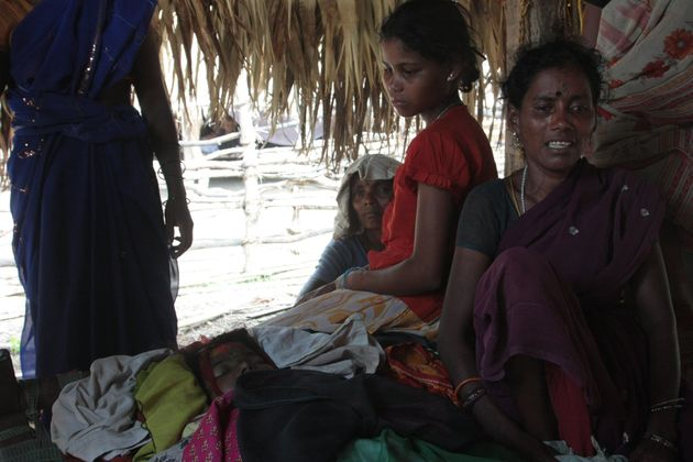 The family of 12 year old Kaka Saraswati sit by her corpse. Seventeen villagers were killed by Indian...