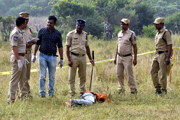 Police personnel stand next to the body of a man at the site where Police officers shot dead four detained...