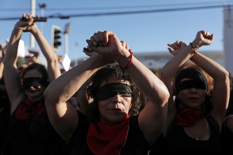 Women rights activists and people wearing blindfolds participate in a protest opposing violence against...