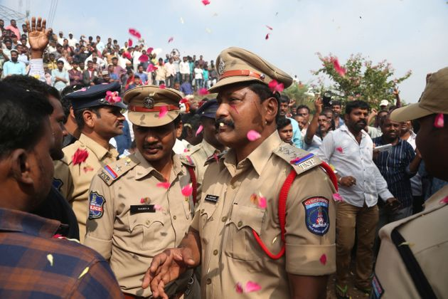 People throw flower petals on the policemen guarding the area where rape accused were shot, in Shadnagar...
