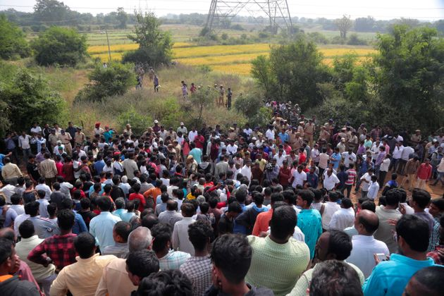 People gather near the site where four men suspected of raping and killing a woman were killed in Shadnagar...