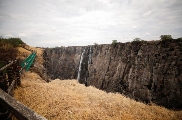 Visitors walk over the bridge at Victoria Falls, which is currently suffering from extreme