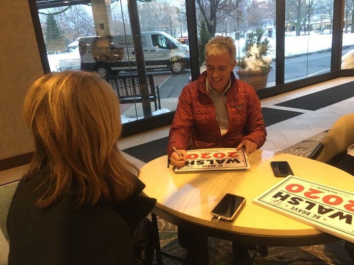 The GOP presidential hopeful and his wife, Helene Walsh, sign campaign posters in New Hampshire.
