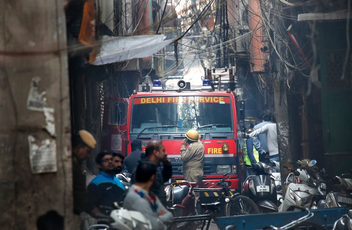 A fire engine stands by the site of a fire in an alleyway, tangled in electrical wire and too narrow for vehicles to access,