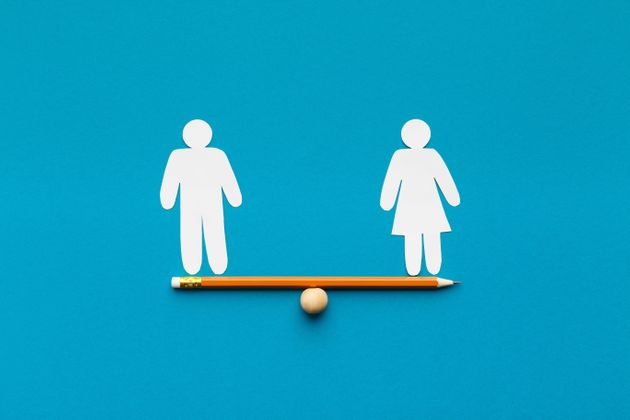 Gender equality in corporate world. Figures of man and woman on pencil seesaw, blue background, copy
