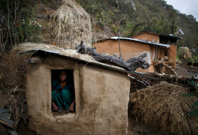 A 14-year-old girl sits inside a chhaupadi shed in the hills of Legudsen village in Achham district in...
