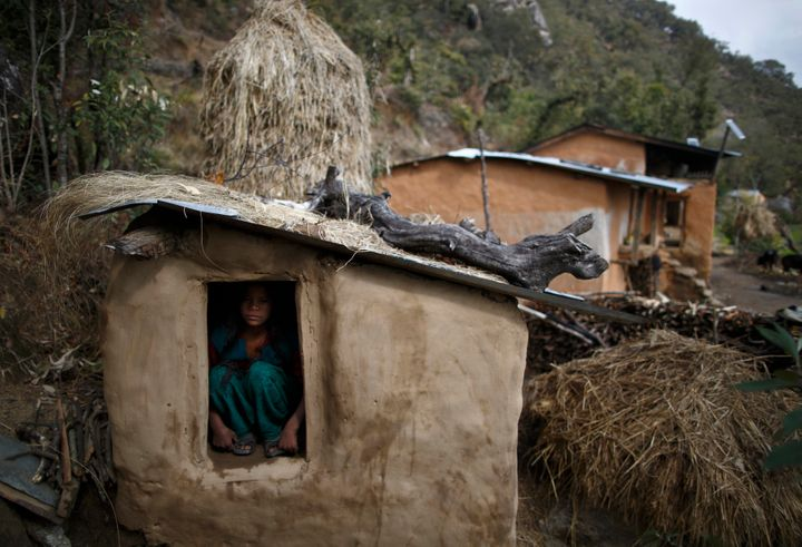 A 14-year-old girl sits inside a chhaupadi shed in the hills of Legudsen village in Achham district in western Nepal in 2014.