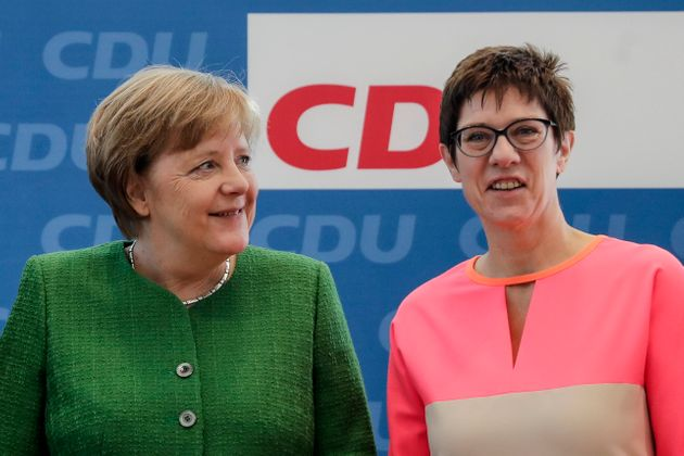 FILE - In this Monday, Feb. 19, 2018 file photo German Chancellor Angela Merkel, left, and the governor...