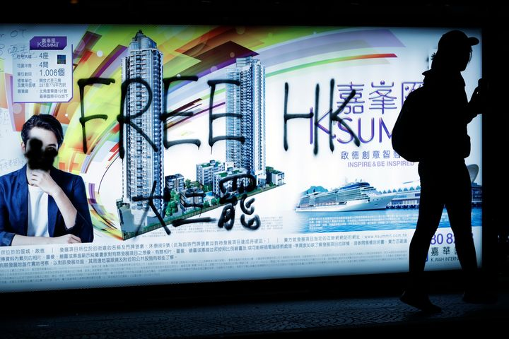 A pro-democracy protester walks by a spray-painted advertisement as demonstrators gather on a street during a protest in Hong