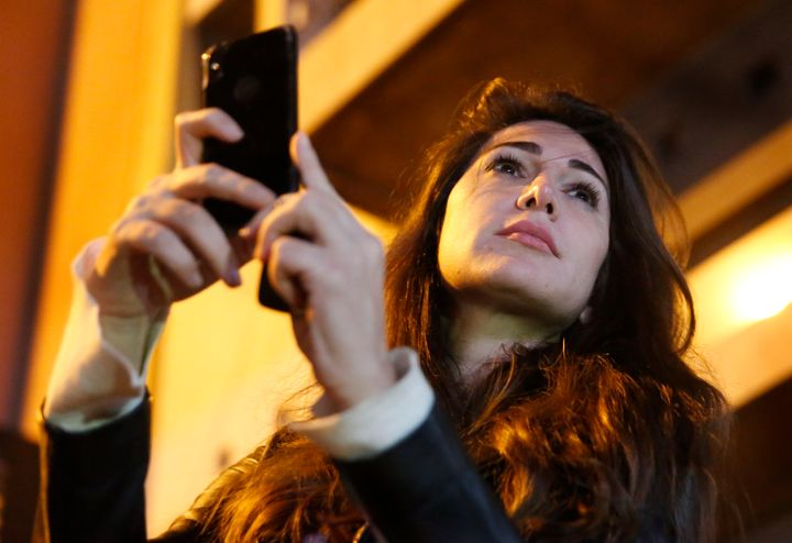 In this Wednesday, Dec. 4, 2019 photo, Lebanese anchorwoman Dima Sadek uses her cellphone to film an anti-government protest,