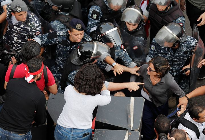 In this Friday Oct. 25, 2019, MTV television reporter Nawal Berry, right, is protected by riot policemen after she was attack