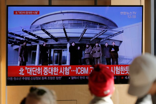 People watch a TV news program reporting North Korea's announcement with a file footage of North Korean...