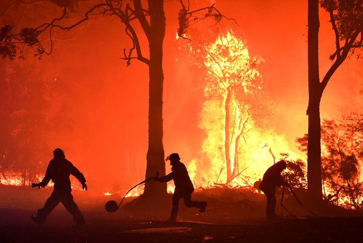 Rural Fire Service (RFS) volunteers and NSW Fire and Rescue officers fight a bushfire encroaching on properties near Termeil, Australia.