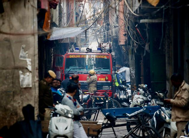 A fire engine stands by the site of a fire in an alleyway, tangled in electrical wire and too narrow...