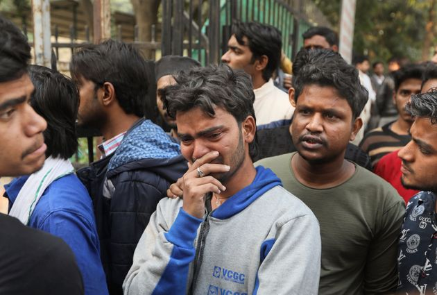 Mohammad Zakir, center, who lost his brother in a fire cries as he waits for the body outside a mortuary...
