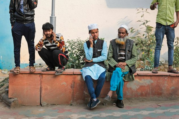 People wait to collect bodies of relatives who died in a fire in New Delhi, Dec. 8,