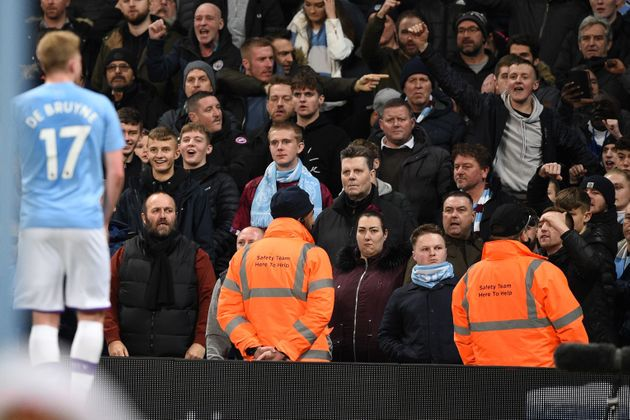 Manchester City's Belgian midfielder Kevin De Bruyne (L) tries to calm City fans jeering and throwing...