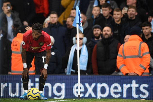 Manchester United's Brazilian midfielder Fred (L) tries to take a corner kick after being pelted with...