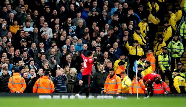 Manchester United's Fred holds an area of his back near Manchester City fans in the corner during the...