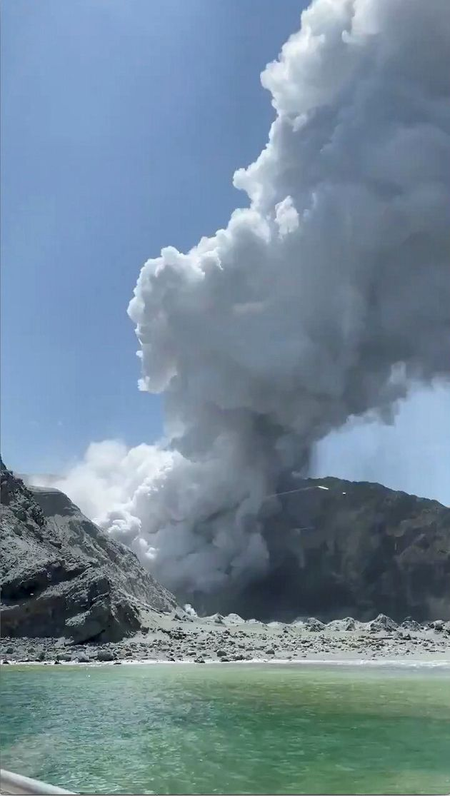 Thick smoke from the volcanic eruption of Whakaari, also known as White Island, is seen from a distance...