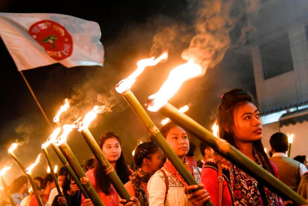 Activists of All Assam Students Union (AASU) take part in a torch light procession to protest against...