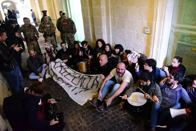 Activists sit after having barged into the building of Malta's Prime Minister Joseph Muscat's...