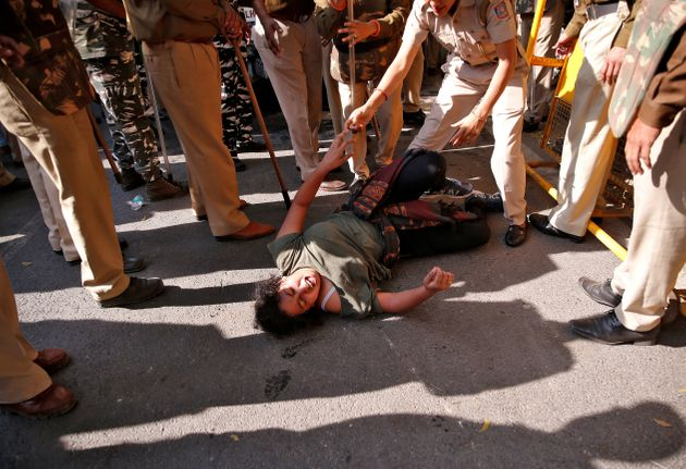 A student of Jawaharlal Nehru University (JNU) reacts as police try to detain her during a protest against...