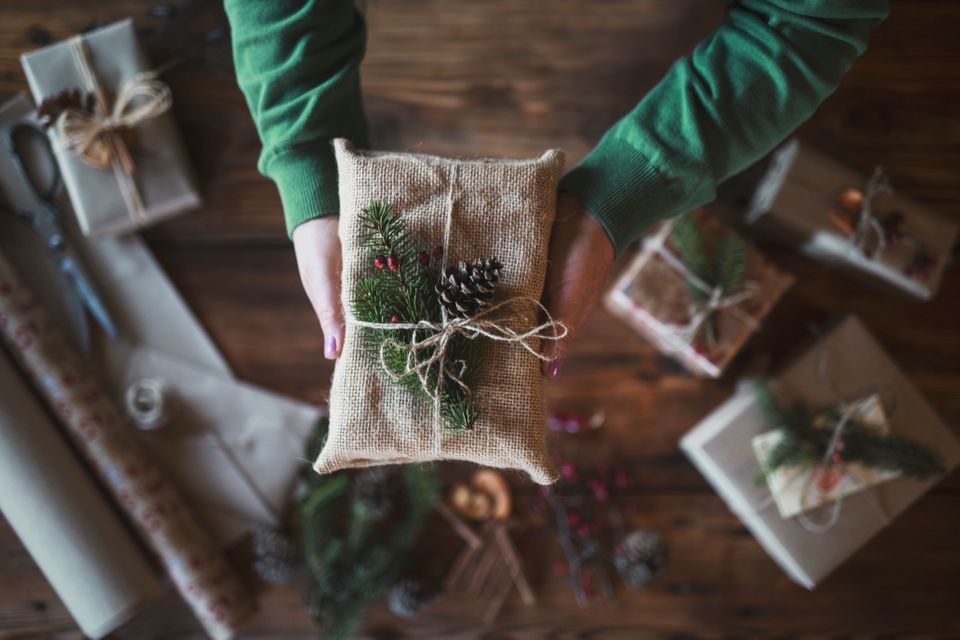 Close up stock photo with unrecognizable female hands holding gift wrapped with textile and natural