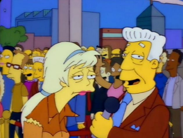 A Kent Brockman lookalike can be seen in the crowd while the newscaster interviews