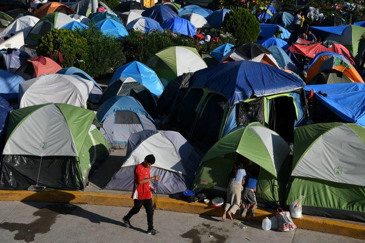 "Migrants, most of them asylum-seekers sent back to Mexico from the U.S. under the ""Remain in Mexico"" program, occupy a makesh"